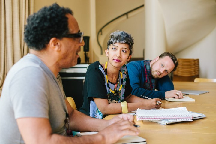 Three people sit at a table, papers and pens in front of them, two turning to look at one who is speaking