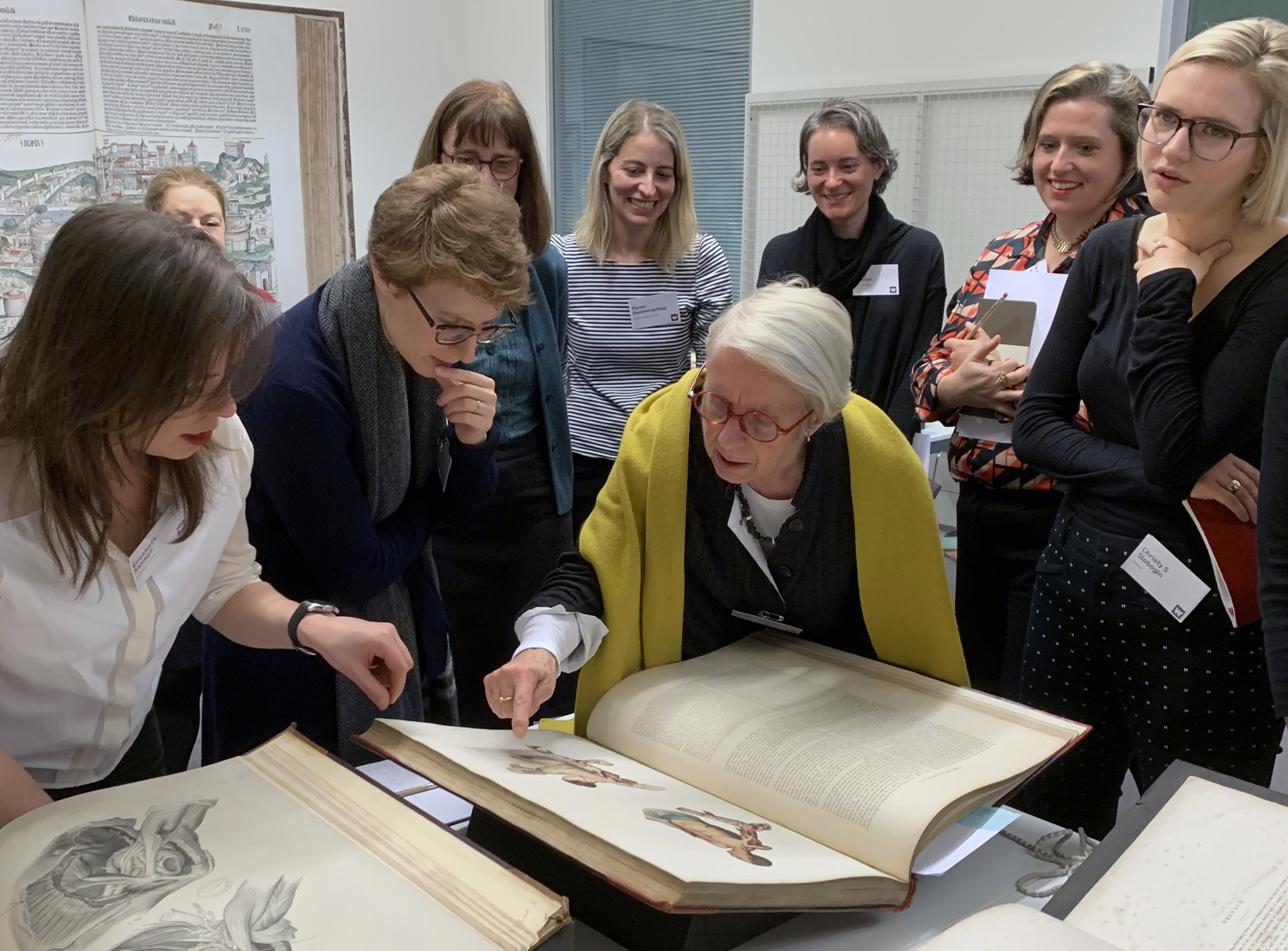 Participants at a workshop considering rare books laid out on a table