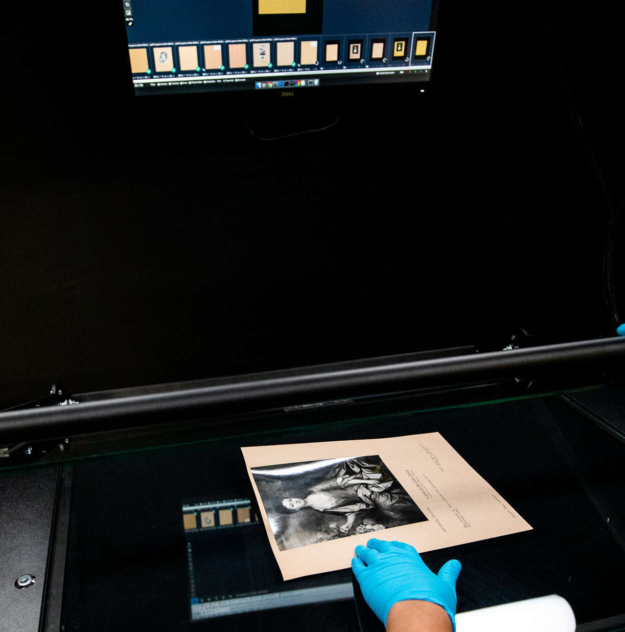 Hand placing photographic mount on to digitisation machine