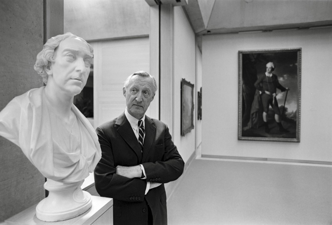 Paul Mellon with arms crossed in the Yale Center for British Art galleries looking at a bust of Thomas, 1st Baron Dartrey